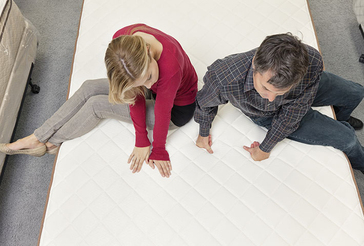 couple testing a mattress in store