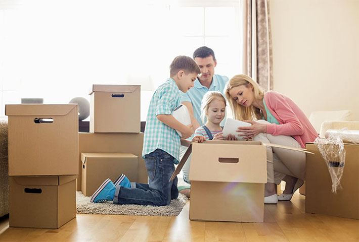 family of four preparing moving boxes