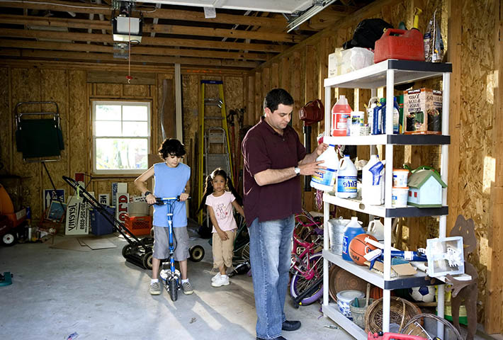 man and his 2 kids in the garage