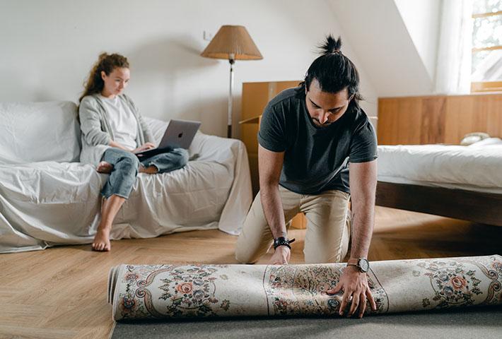 man rolling a rug