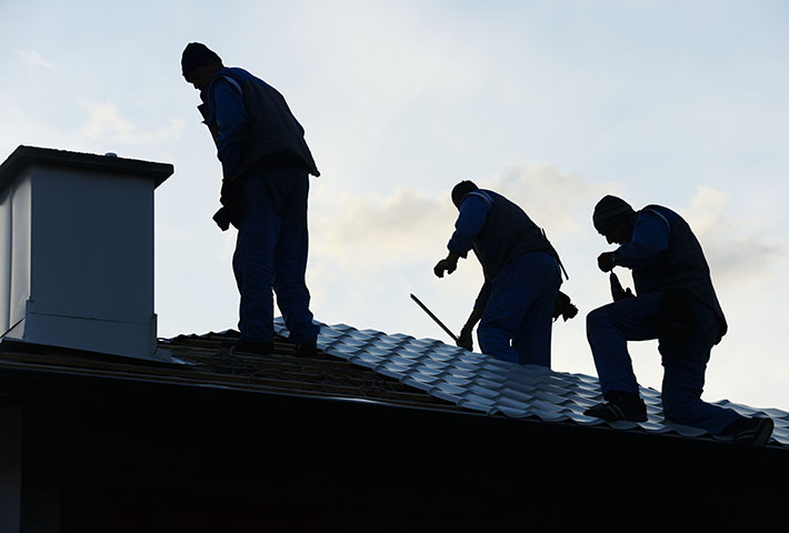 men replacing roof on house