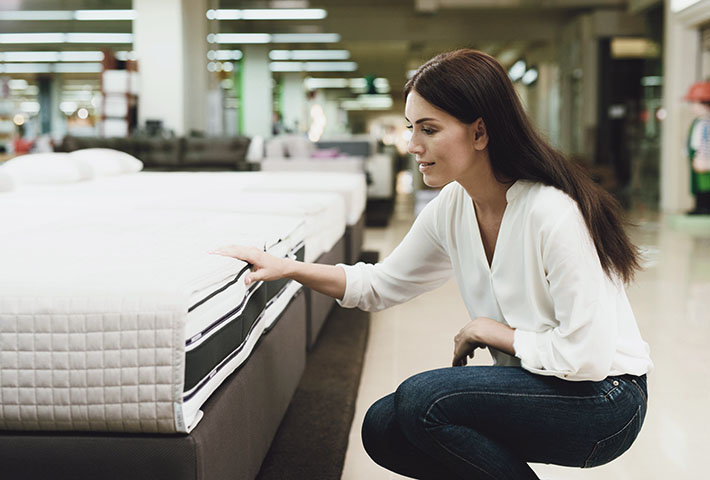woman testing a mattress in store